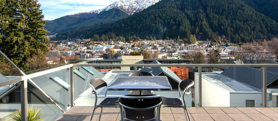 Large balcony/terrace with outdoor table and views over Queenstown.