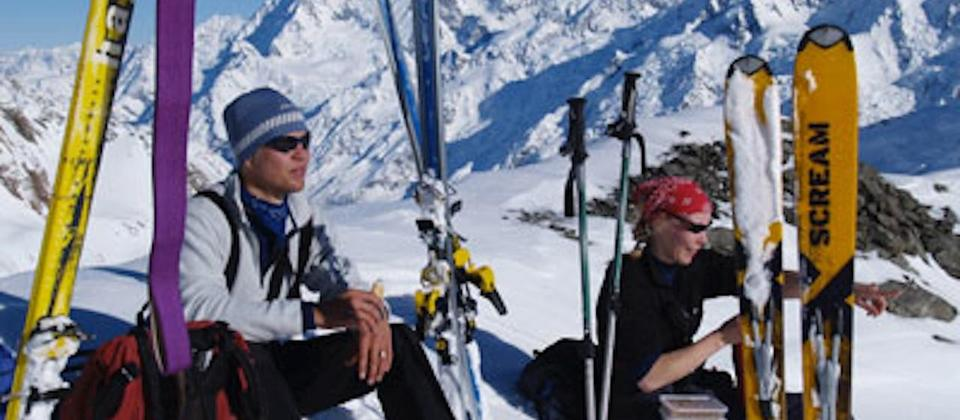 Alpine ski tourers pause for lunch after a ski ascent of Hochstetter Dome at the top of the Tasman Glacier. Mount Cook in the background.