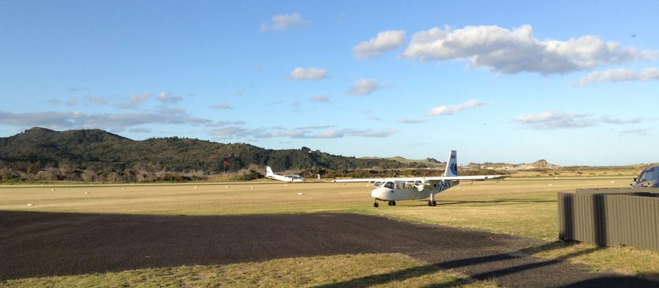 The Fly My Sky Britten Norman Islander landing on a grass runway on Great Barrier Island