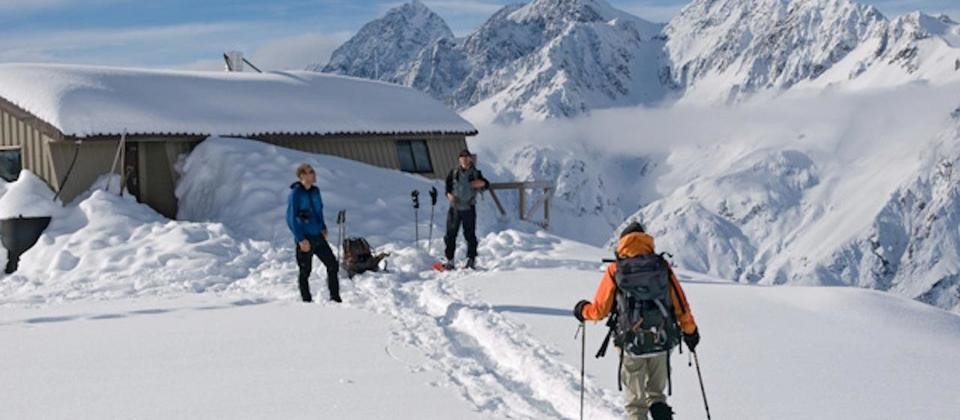 Snowshoers return to Caroline Hut after an ascent of Kaitiaki Peak in winter