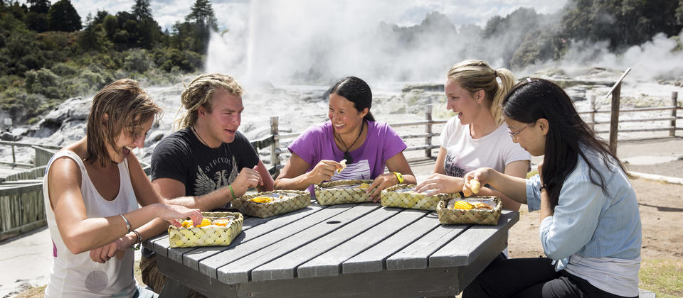 Enjoying steam box lunch at picnic table overlooking Pohutu geyser