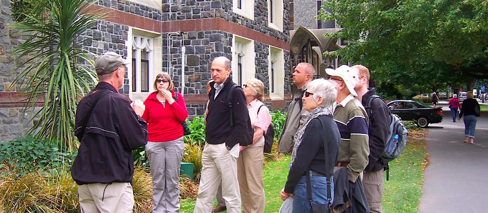Guide discussing heritage building with walkers