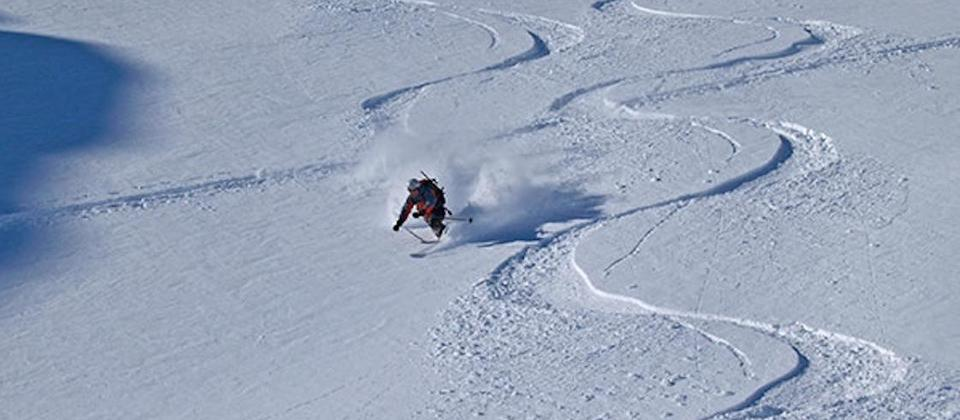 An expert Telemarker shreds the pow at the top of the Tasman Glacier on a 6-day ski touring trip based at Kelman Hut
