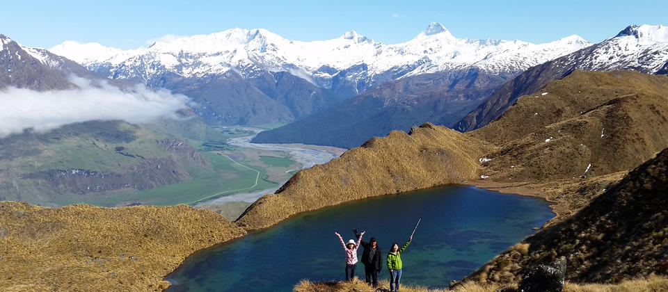 A group enjoying the stunning views out over an alpine lake, the Matukituki Valley and Mount Aspiring National Park.
