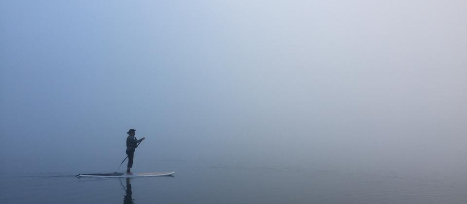 A paddle experiencing the unknown onLake Tikitapu in fog