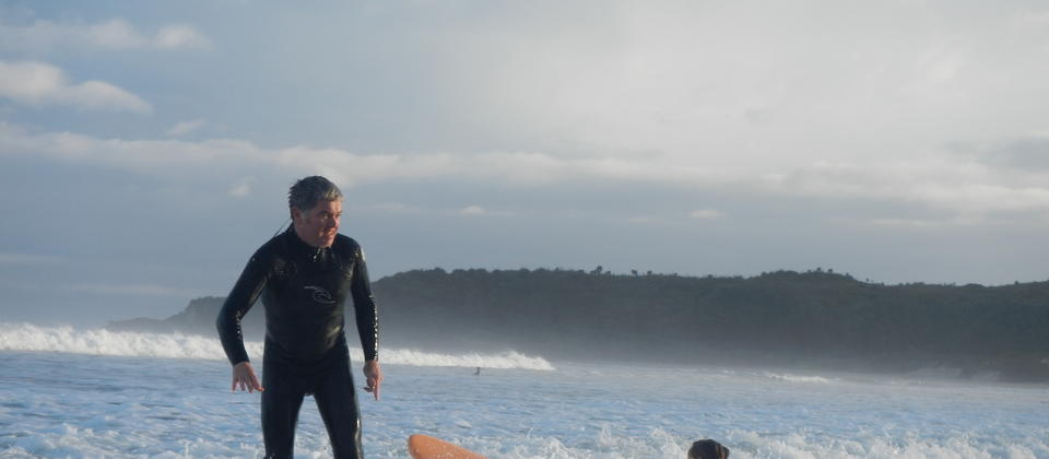 father and daughter surfing together