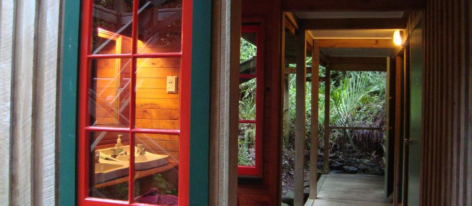 The bathroom facilities are joined by a wooden walkway in lush subtropical gardens.