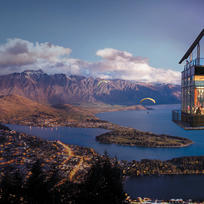 The night time view of the Skyline Queenstown complex from an outdoor seating area.
