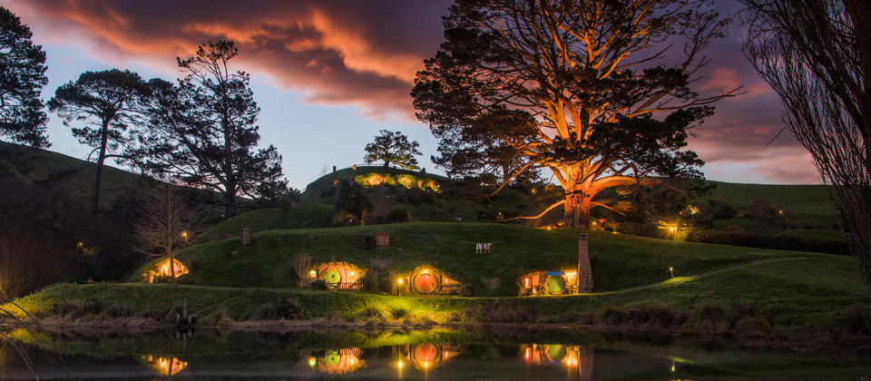 The Hobbiton™ Movie Set in the lush countryside setting of Matamata is a spectacular sight at sunrise or sunset.