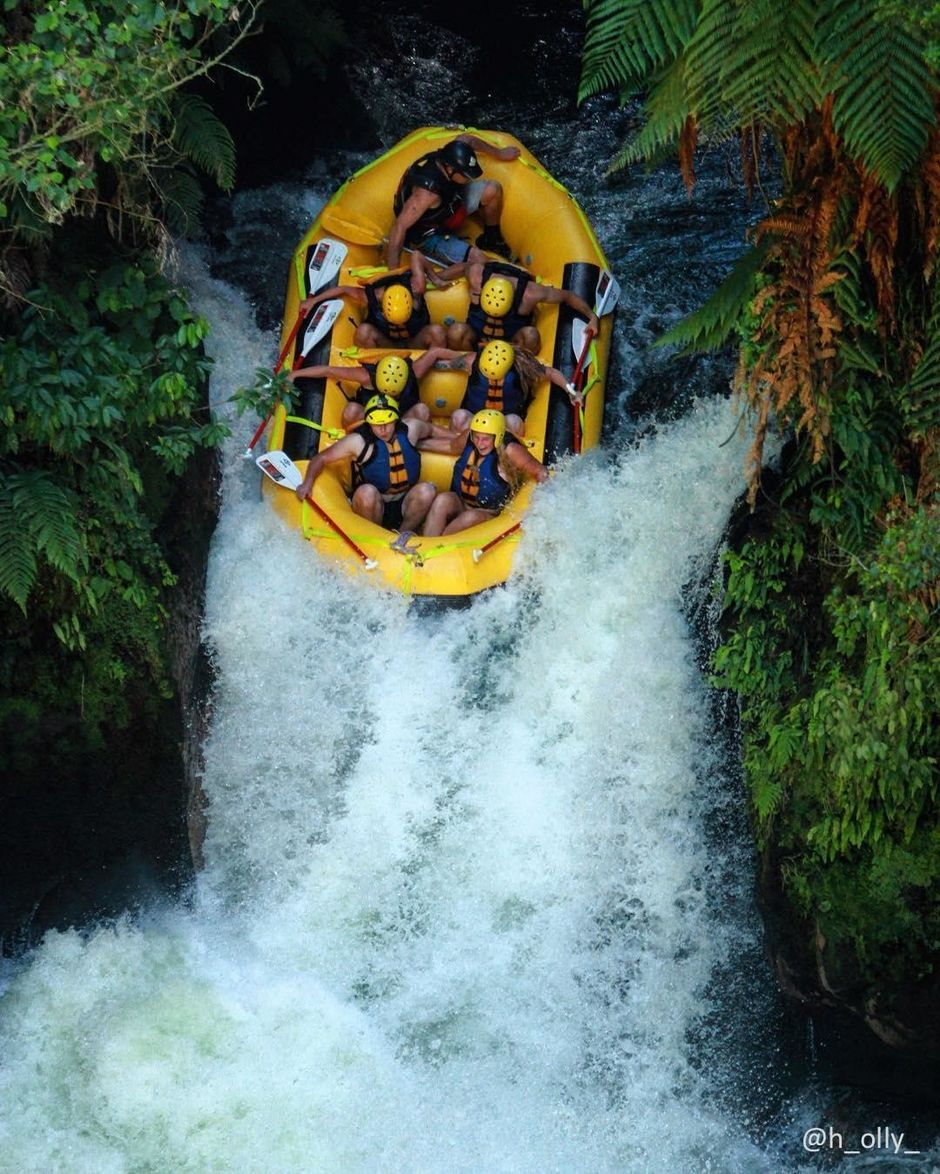 Whitewater rafters brace themselves for a waterfall while rafting the Kaituna River