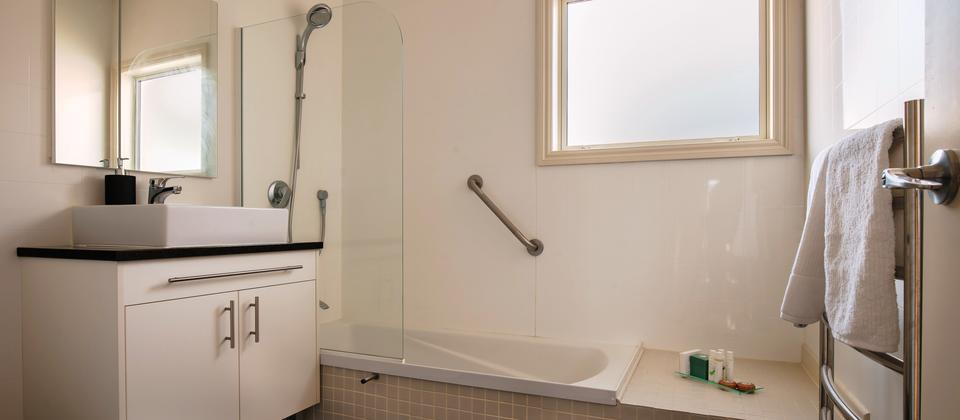 The main bathroom features a bath/shower, basin, toilet, heated floor and heated towel rail.