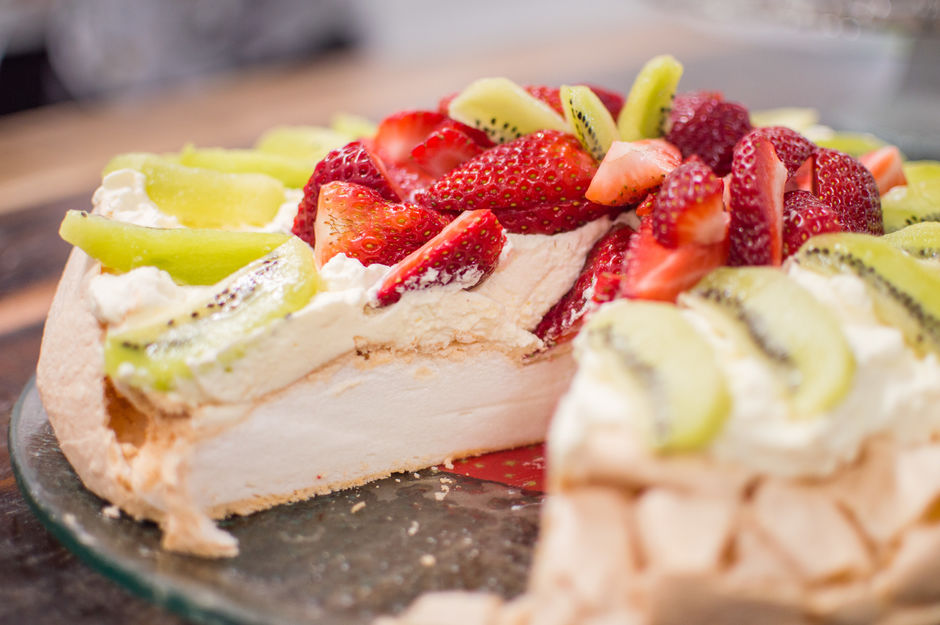 A classic Kiwi pavlova garnished with kiwifruit and strawberries.