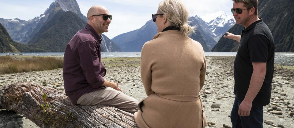 Couple listening to pilots storytelling in Milford Sound.
