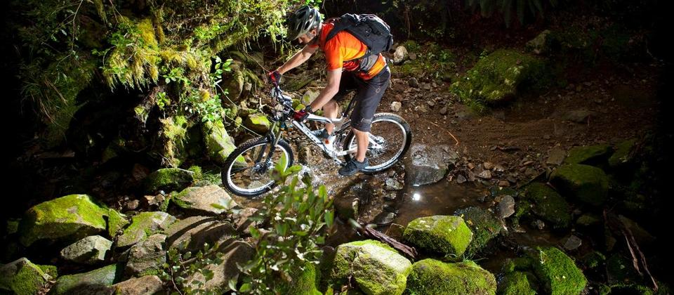 Riding through a creek on the Rameka Track in Golden Bay