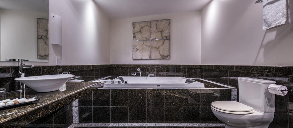 Marbled bathroom featuring a double sized indoor spa and a shower with twin massage heads